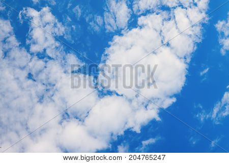 fluffy white clouds on a blue clear sky, background