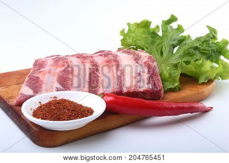 Raw pork ribs with herbs and spices on wooden board. Ready for cooking
