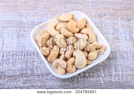 nuts cashews in white bowl on wooden background. Selective focus