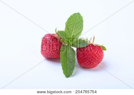 Fresh strawberries and mint leaves isolated on white background. Selective focus