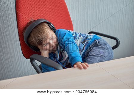 Little boy with headphones sitting at computer in office and looking at monitor