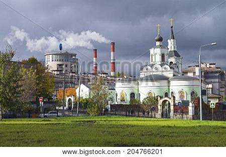 MOSCOW RUSSIA _ OCTOBER 15 2018: Moscow contrasts - building in the style of constructivism the smoking chimneys of the power station and the old Orthodox Church next to each other against the gray autumn sky.