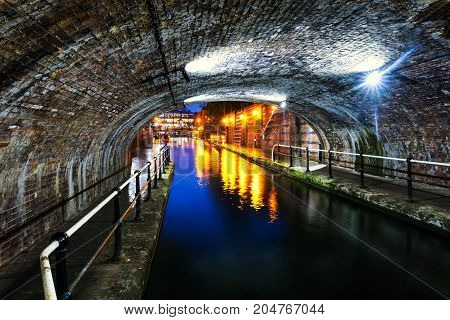 Birmingham, UK. Tunnel in the city center during the rain, illuminated buildings at night, famous Birmingham canal in UK