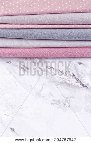 A stack of fabrics on pink gray color over marble table background. Mockup. Flat lay top view