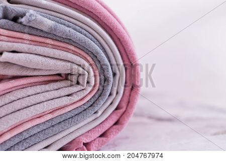 A stack of fabrics are wrapped in a roll on pink gray color over marble table background. Mockup. Flat lay top view