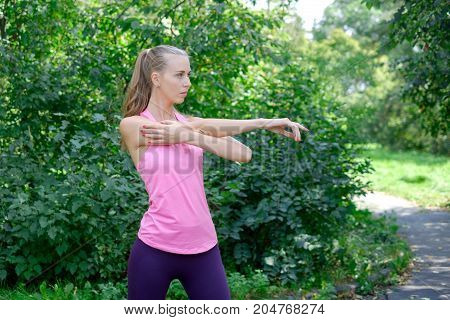 Portrait of sporty woman doing stretching exercises in park before training. Female athlete preparing for jogging outdoors. Runner doing side lunges. Sport active lifestyle concept. Full length