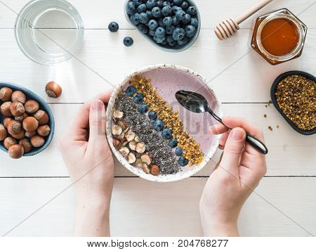 Eating healthy breakfast bowl. Buckwheat smoothie porrige, fresh berries, seeds and nuts, bee pollen in white ceramic bowl in woman hands on table. Clean eating, dieting, detox, vegetarian food concept