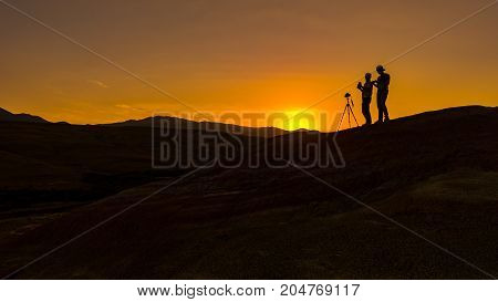 Nature photographers in mountains at sunset time