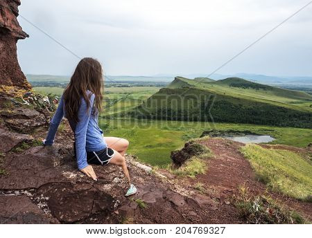 The girl sits on the mountain and looks into the lake. At the bottom are green fields.