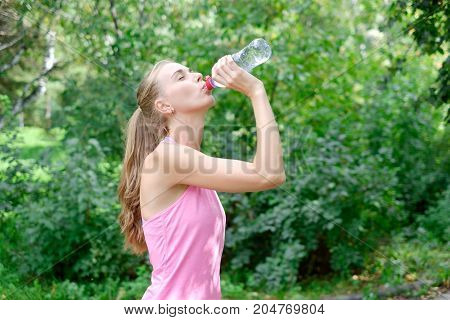 Attractive young sportwoman finished her work out and now drinking water and smiling in the park.