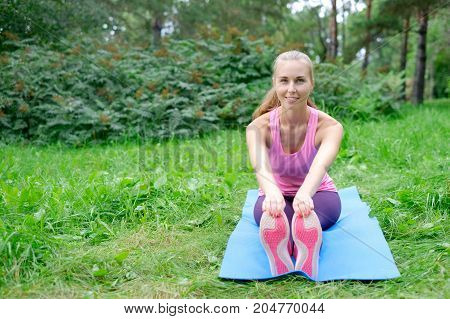 fitness, sport, training, park and lifestyle concept - smiling woman doing exercises on mat outdoors.
