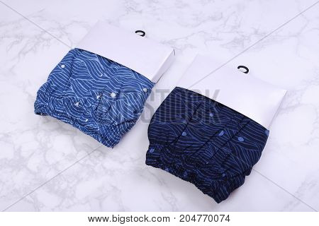 Blue men short in packaging on marble background
