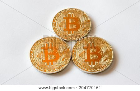 On a grey background are gold coins of a digital crypto currency Bitecoin.