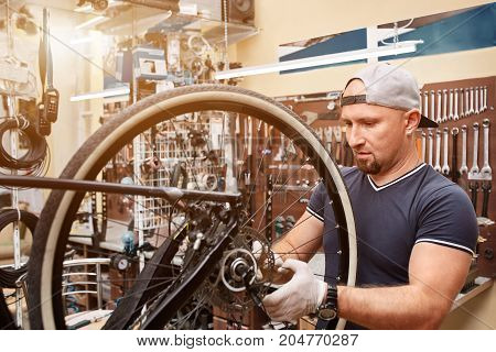 Handsome Mechanic repairing a mountain bike in a workshop