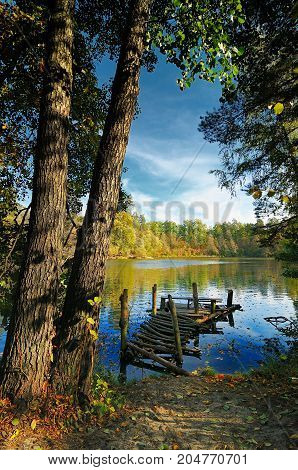 Beautiful tranquil scene with old fishing platform on the fall lake