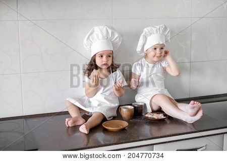 two little baker girls are drinking tea with a pabcakes in the kitchen.