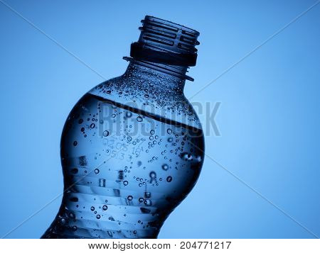 one open bottle of sparkling water is isolated on a blue background