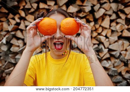 Young Funny Girl With Bright Make-up, Wear On Yellow Shirt Hold Two Orange At Eyes Against Wooden Ba