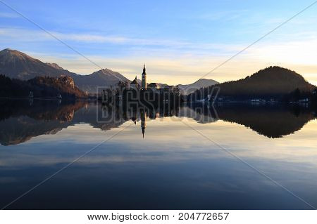 The Assumption Church in the island of Bled with the castle nearby reflecting in the water.
