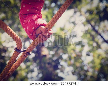 kids outdoor safety concept- child hand climbing on playground
