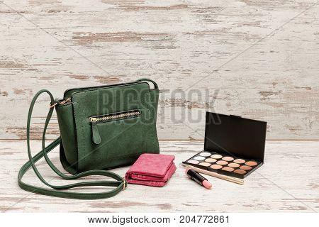Little Green Ladies Handbag, Pink Purse, Eyeshadow Palette And Lipstick On Wooden Background. Fashio
