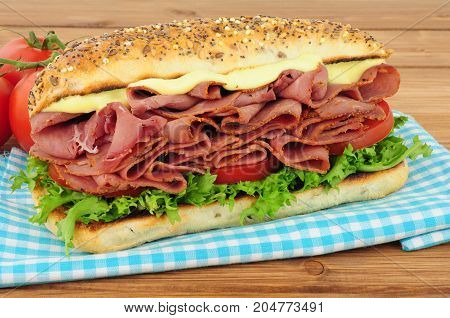 Spicy pastrami meat and salad sandwich in a seed covered bread roll isolated on a white background