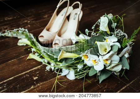 Beautiful wedding beige shoes with high heels and a bouquet of white and green flowers on a vintage wooden floor, preparing for the wedding, details