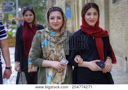 Fars Province Shiraz Iran - 18 april 2017: Young Iranian women dressed in hijab are walking along a city street with smartphones in their hands.