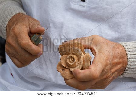 Wood carving, hand of the master working with a wooden surface, is a professional engaged in carving flower rose.