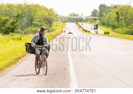 A Man Is Riding Along The Road On A Bicycle, Vinales, Pinar Del Rio, Cuba. Copy Space For Text.