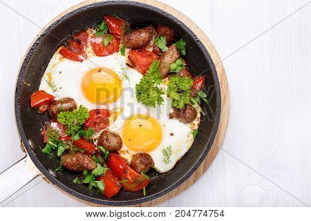 Breakfast. Fried eggs with sausages and vegetables in a frying pan fried eggs. Top view.