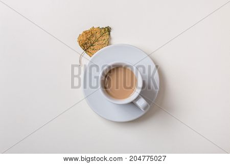 Isolated cup of coffee on saucer with autumn dry yellow leaf on white background. Top view. Flat lay.