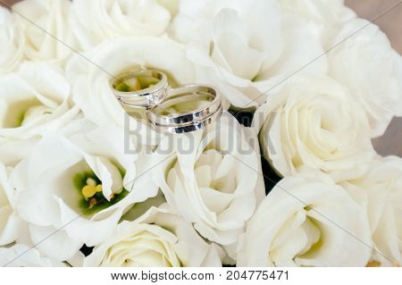 Wedding rings closeup lying on the bouquet of white roses