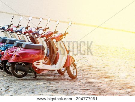 Colorful moped scooter parking. Transport wheel. Summer sunlight flare.