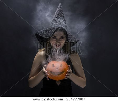 Attractive witch with smoky pumpkin in her hands on black background