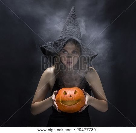 Serious  witch with smoky pumpkin in her hands on black background
