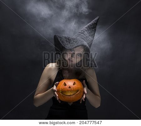 Angry witch with smoky pumpkin in her hands on black background