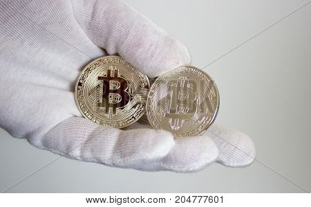 On hand in white glove are silver coins of a digital crypto currency - Bitcoin.