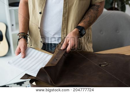 Musician Putting Music Notebook Into Bag