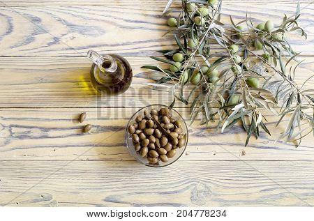 Marinated olives in a bowl, a branch with fruits and olive oil in a jug on a wooden table close-up