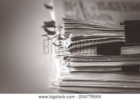 extreamely close up the report paper stacking of office working document with paper clip folder vintage color tone