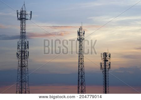 Three mobile phone communication tower transmission signal leash in evening sky