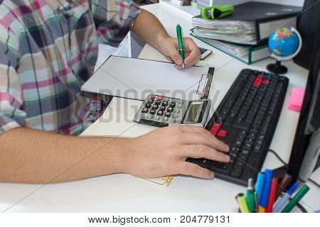 Image of male hand pointing at business document during discussion at meeting. Male Accountant Calculating Tax In Front Of Computer At Desk