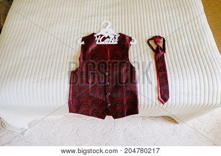 Wedding red vest on a hanger and tie lying on a bed with beige blanket