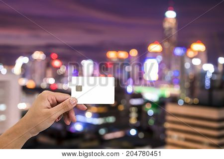hand hold blank card on cityscape bokeh Blurred Photo cityscape at twilight time