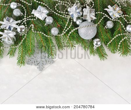 Silver Christmas Decorations On A Spruce Branch On A White