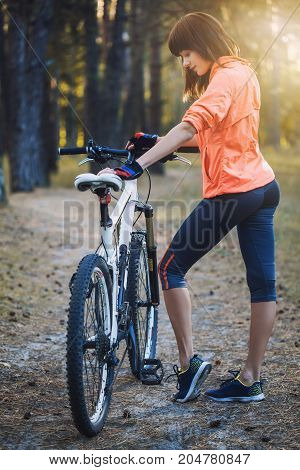 cute woman cyclist cycling mountain bike on Pine forest trail