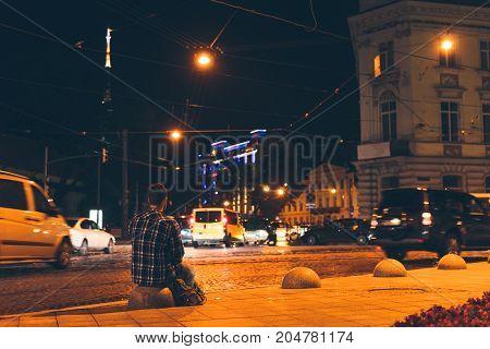 man sitting and looking at night city, long exposure