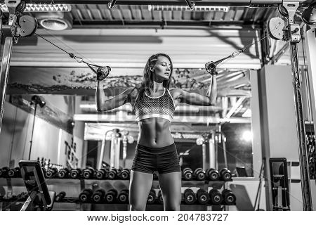 woman flexing biceps muscles on cable machine in gym