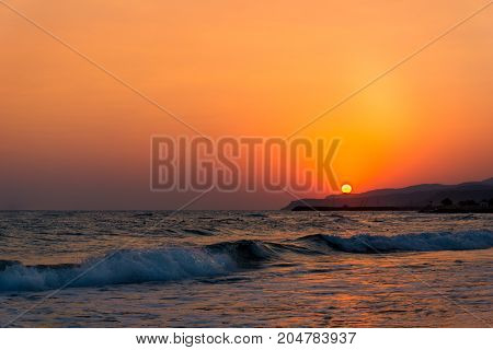View on a amazing Sunset at the Beach. Close-up of a beautiful deserted Beach in front of a warm Sunset. Travel and Beach Background